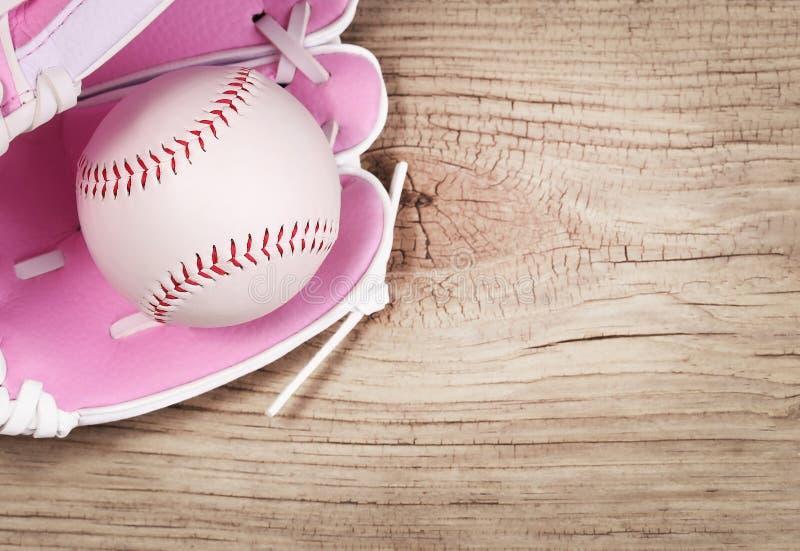 baseball Ball im rosa weiblichen Handschuh über hölzernem Hintergrund stockfotografie