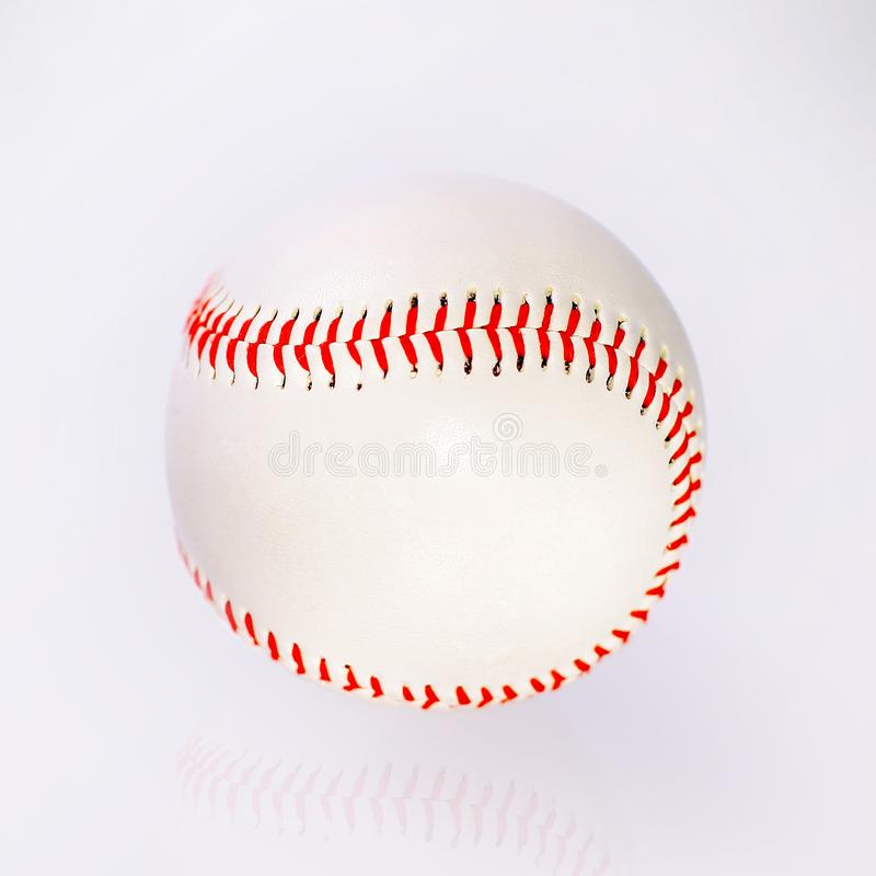 Baseball ball with red firmware on the table with reflection royalty free stock images