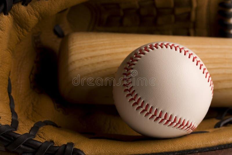 Baseball and baseball bat in glove stock images