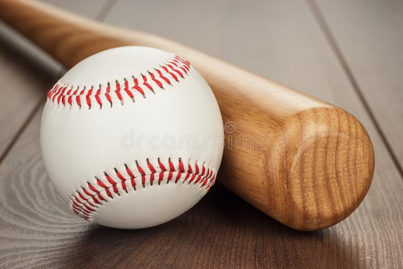 Closeup of baseball bat and ball on wooden table royalty free stock photos
