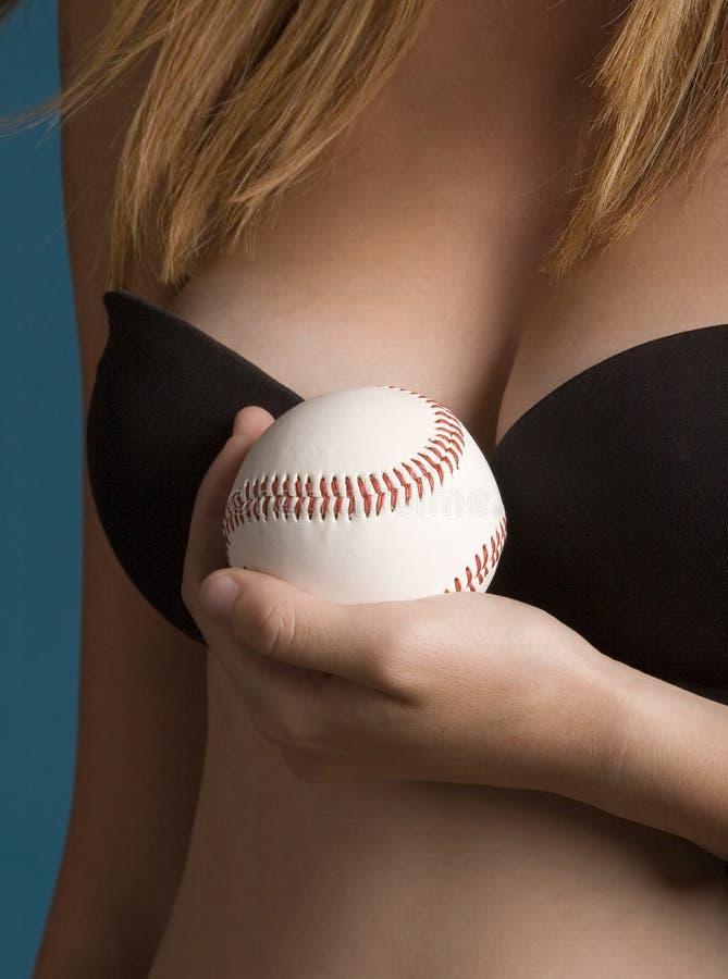 Baseball and breasts. Close-up of baseball and breasts stock image