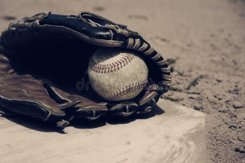 Baseball che risiede nel guanto sul campo, stile d'annata fotografie stock
