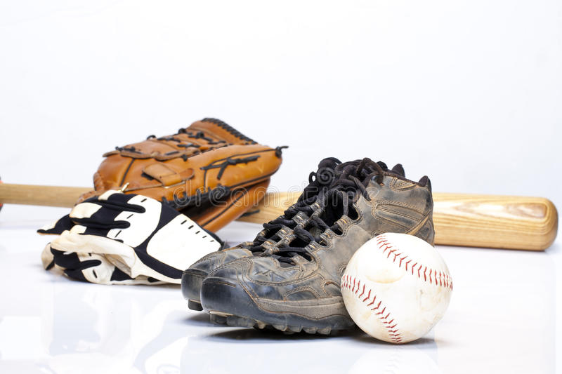 Baseball Cleats. Used baseball cleats against a glove, softball, bat, and batting gloves on a white background stock image