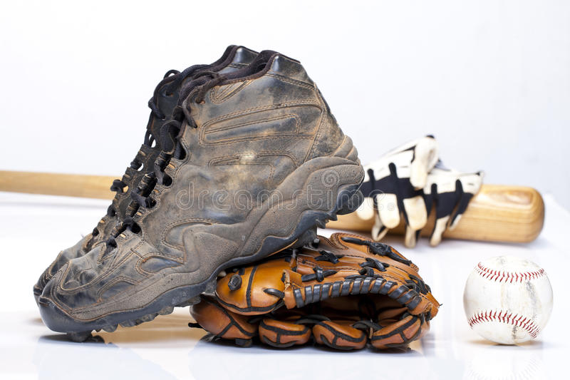 Baseball Cleats. Used baseball cleats against a glove, ball, bat, and batting gloves on a white background stock photos