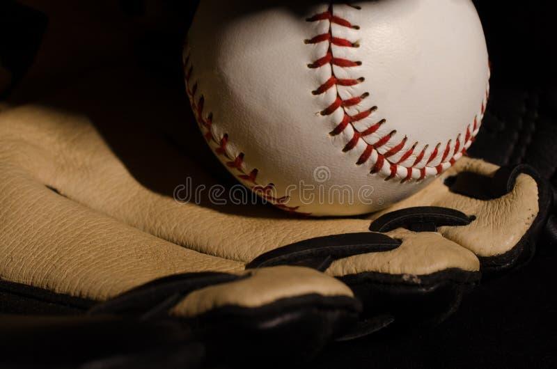Baseball con il guanto su fondo nero fotografia stock