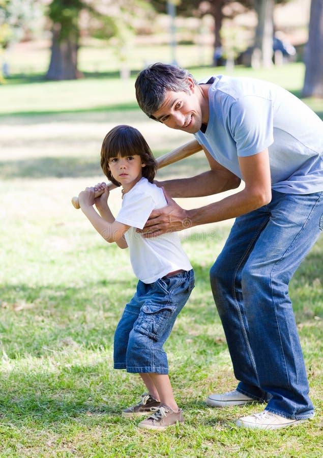 Baseball d'istruzione sorridente del padre al suo figlio fotografie stock