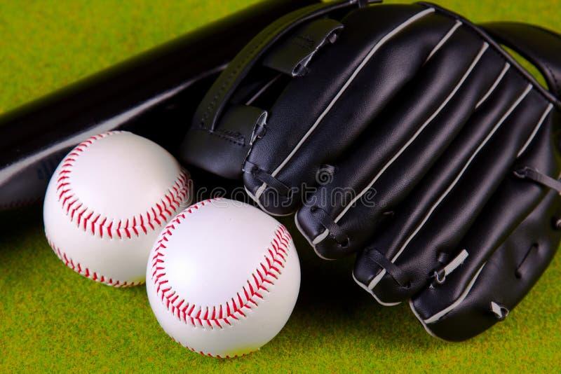 Baseball Equip. Baseball Balls and glove on green background stock image