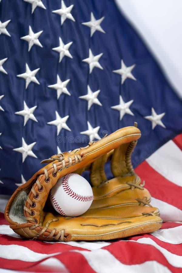 Baseball Glove, Ball & USA Flag - vertical. A well worn baseball glove holding baseball resting on USA flag royalty free stock photography