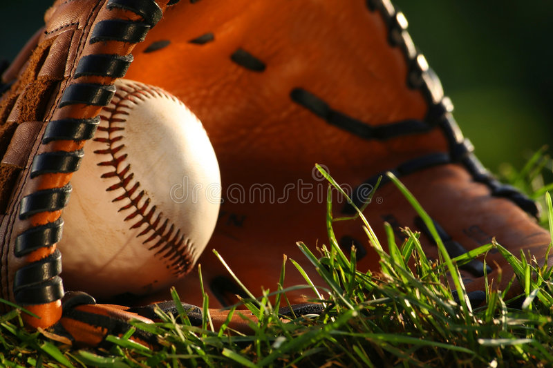 Baseball and glove closeup. Baseball and glove on the grass royalty free stock photography
