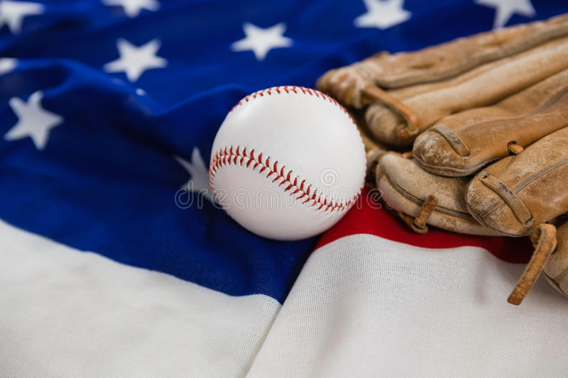 Baseball and gloves on an American flag. Close-up of baseball and gloves on an American flag royalty free stock image