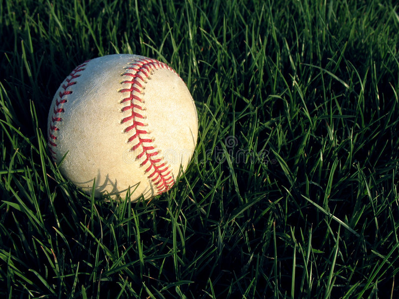Baseball in grass stock photography