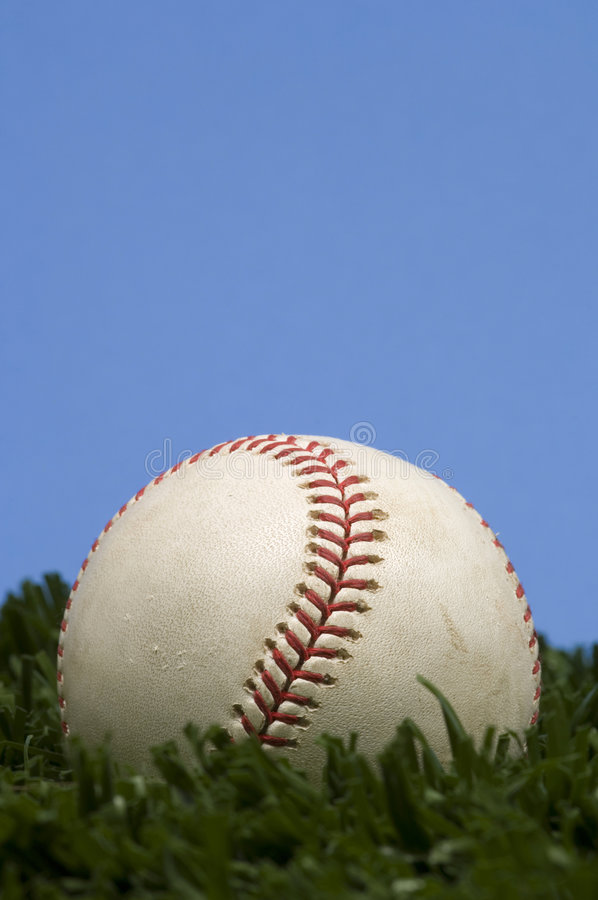 Baseball on Grass in front of blue sky royalty free stock images