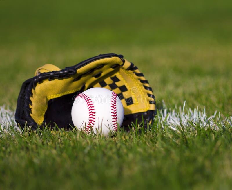 Baseball in guanto giallo sul campo con la linea delle yard e l'erba immagini stock libere da diritti