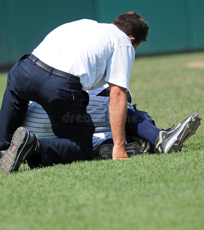 Baseball injury - trainer tends to player