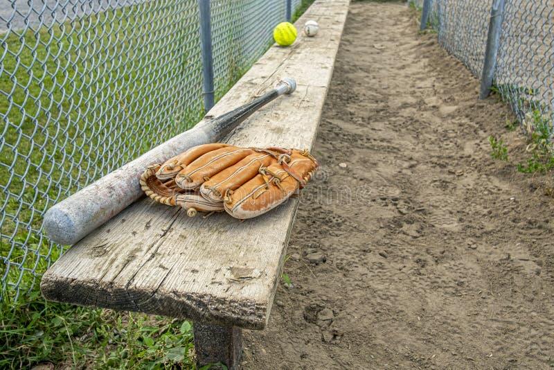 Baseball-knuppels en -ballen op een houten bank in een park stock afbeelding