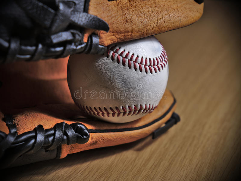 Baseball leather glove with ball on a wooden surface royalty free stock image