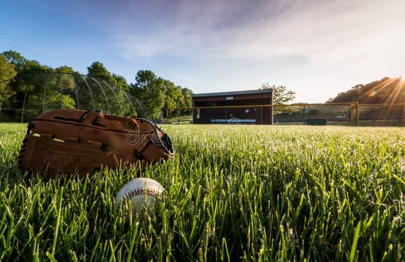 Baseball och handske på gräs nära dugout i otta royaltyfria foton
