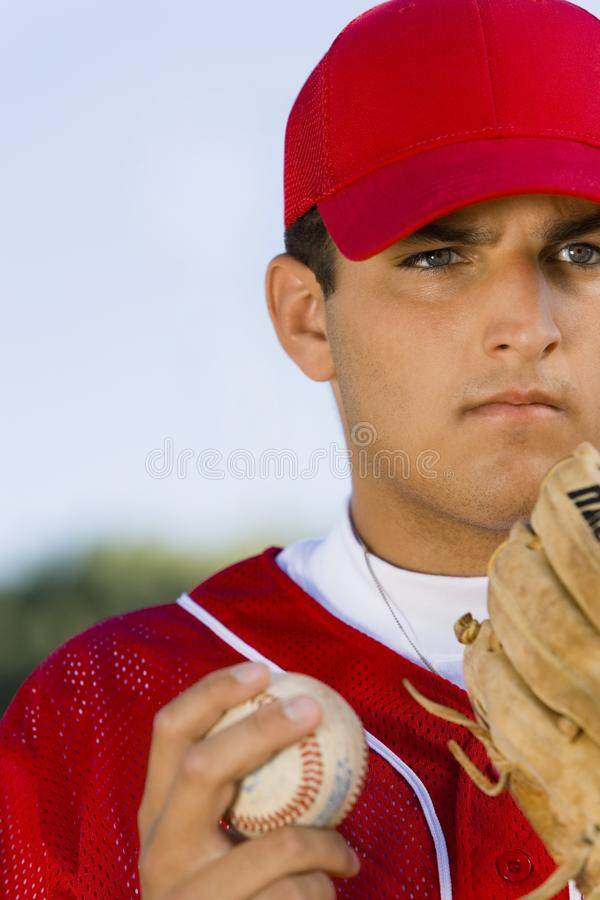 Baseball pitcher holding glove and ball royalty free stock photography