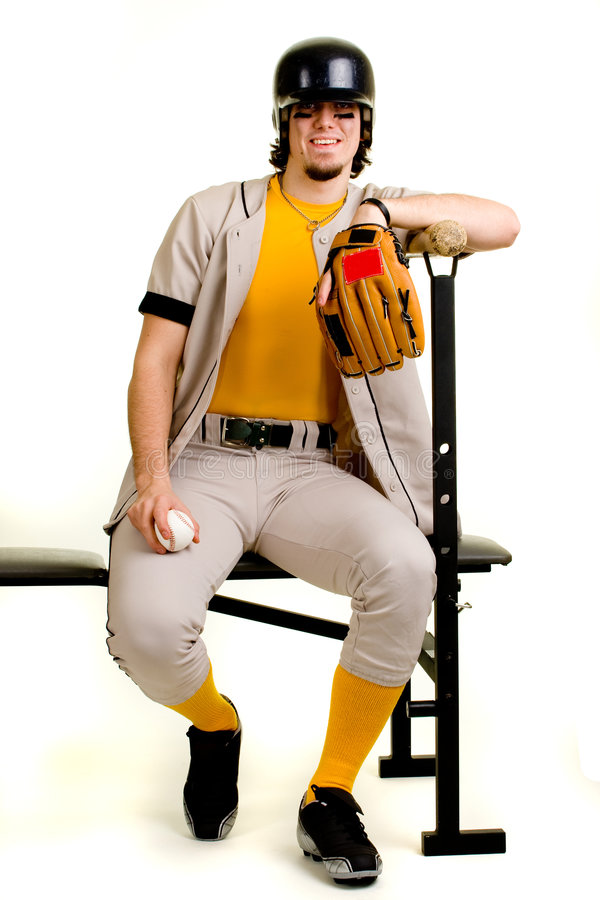 Baseball Player. A young male baseball player sitting on a weight bench stock photo
