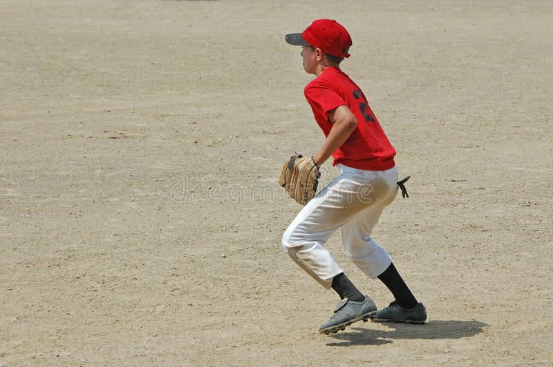 Baseball player fields a ground ball. A boy red shirt and hat with white pants moves to field a ground ball royalty free stock image