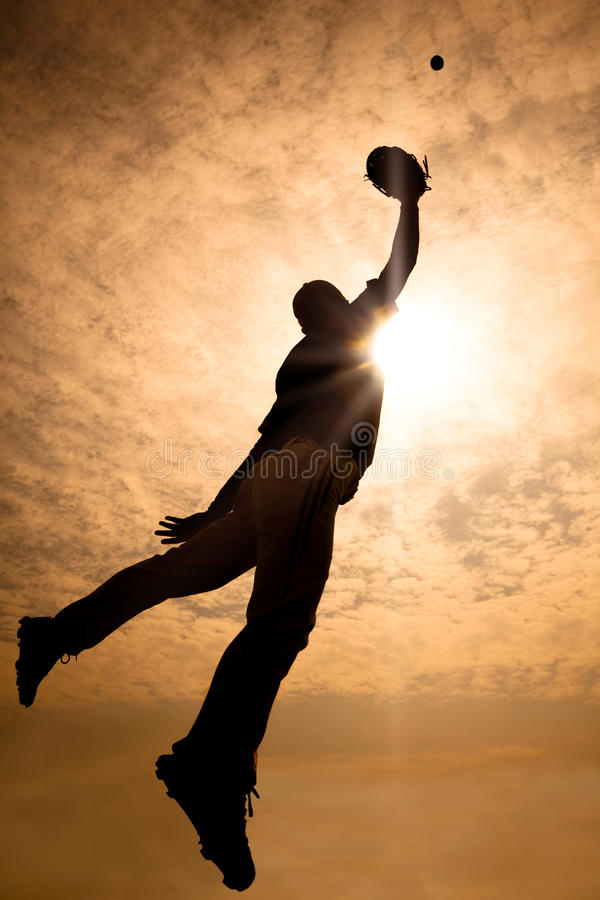 Baseball player jumping into air to make the catc. The silhouette of baseball player jumping into air to make the catch royalty free stock image