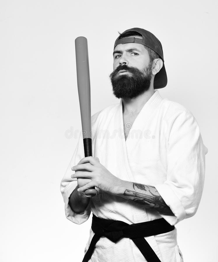 Baseball player with suspicious face holds green baseball bat. Master gets ready to fight. Man with beard in kimono. Baseball player with suspicious face holds royalty free stock photos
