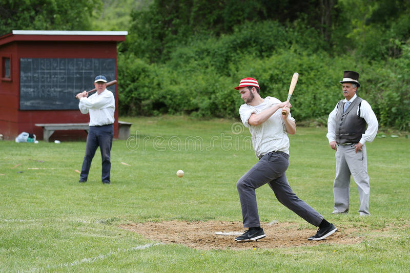 Baseball player in 19th century vintage uniform during old style base ball play. OLD BETHPAGE, NEW YORK - MAY 22, 2016: Baseball player in 19th century vintage stock photos