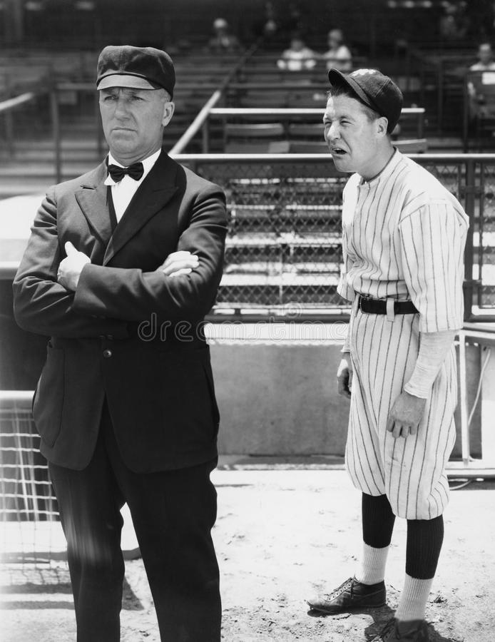 Baseball player and umpire. (All persons depicted are no longer living and no estate exists. Supplier grants that there will be no model release issues stock photography