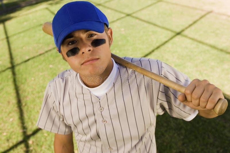 Baseball-Spielerholding-Baseballschläger auf Schulter stockfotografie