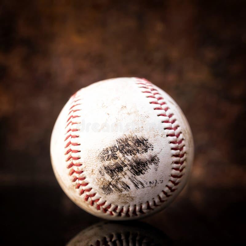 Baseball sporco usato davanti a fondo marrone immagini stock