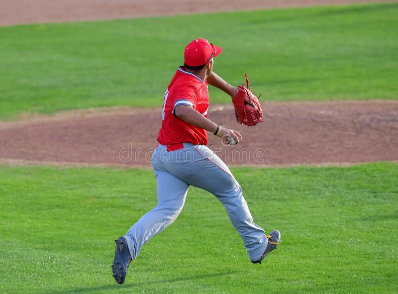 Baseball Third baseman fielding the ball and making a strong throw to first base. Baseball player catching a ground ball and throwing for an out to first base royalty free stock photos