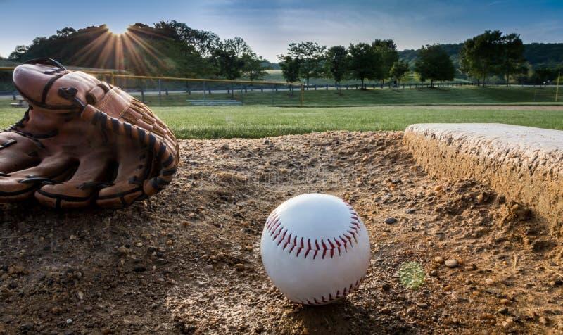 Baseball und Handschuh auf dem Hügel des Werfers am frühen Morgen lizenzfreies stockfoto
