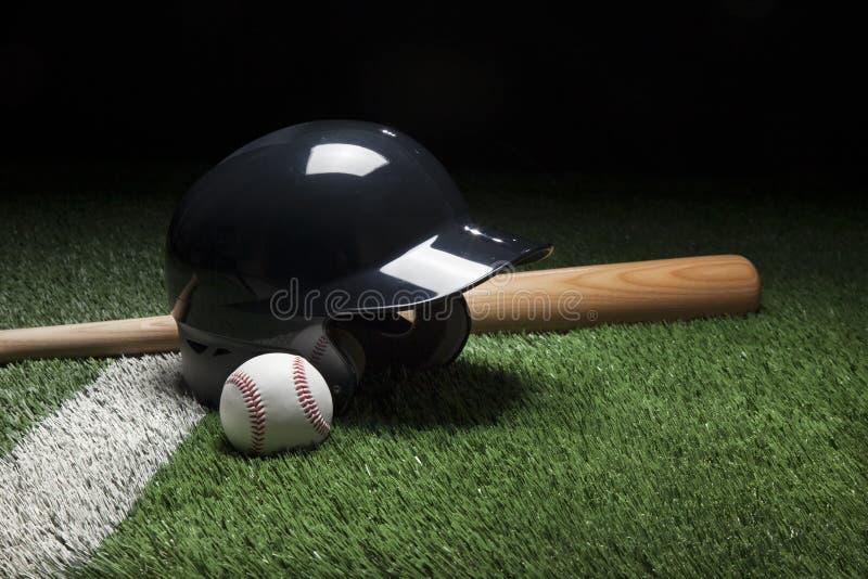 Baseballa uderzenia kijem hełma piłka na polu z lampasem i nietoperz obraz royalty free