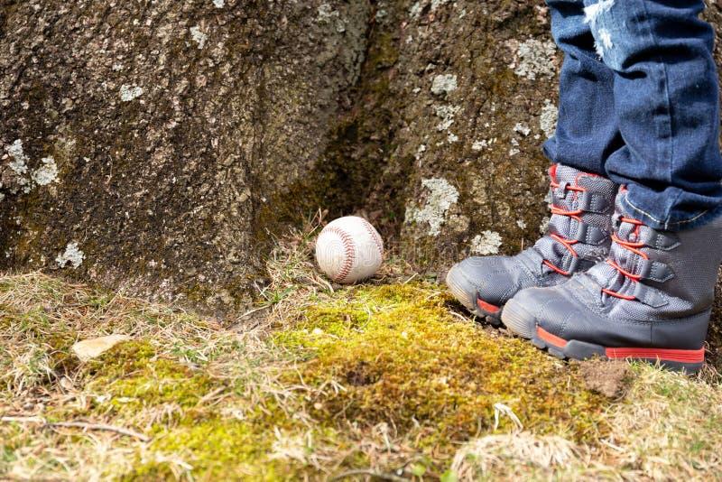 Baseballball und Kinderfuß unter dem großen Baum stockfotos