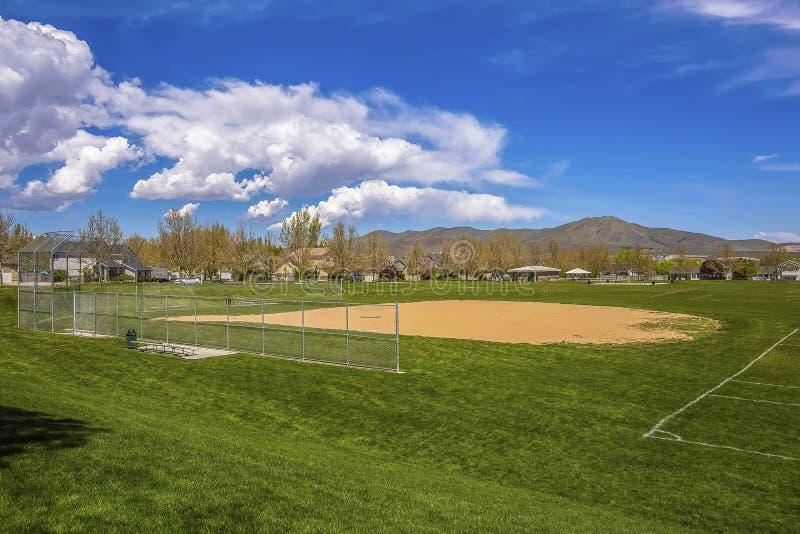Baseballfält med sikt av berget och molnig blå himmel på en solig dag arkivfoto