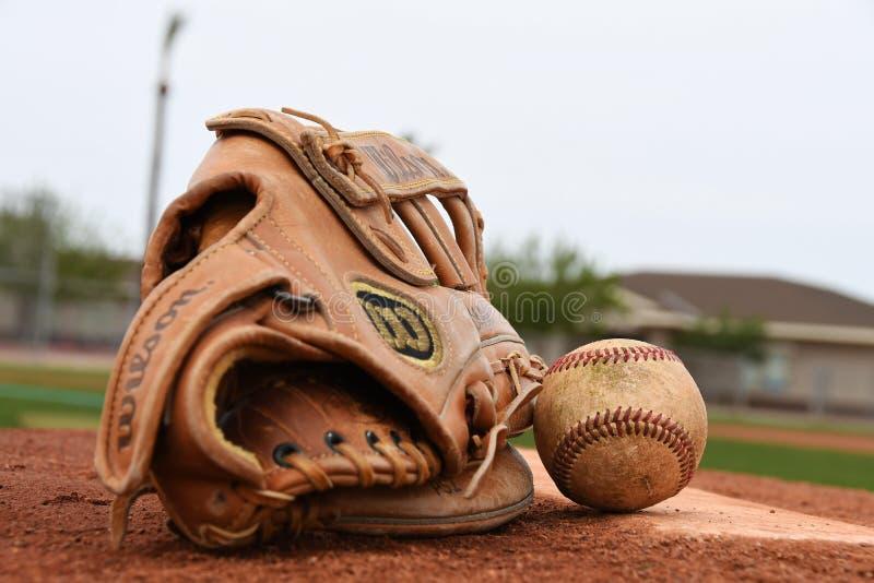 Baseballhandschuh und Baseball auf einem Nicken-Hügel stockfotografie