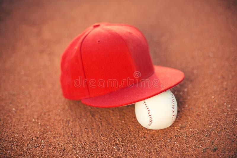 Baseballmütze und Ball auf Feld stockbilder