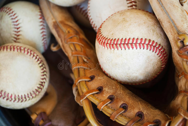 Baseballs and glove in bucket-closeup stock images