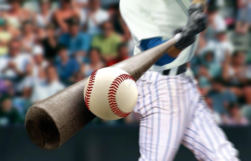 Baseballspieler schlagen Ball mit Fledermaus in der Nähe stockbild