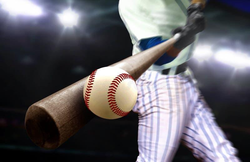 Baseballspieler schlagen Ball mit Schläger in der Nähe von Stadionleuchten lizenzfreie stockfotos