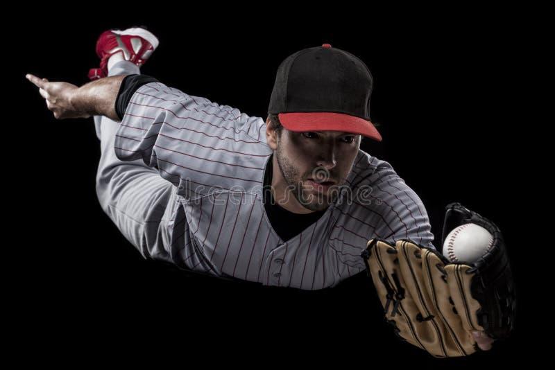 Basebollspelare på en röd likformig. arkivbild