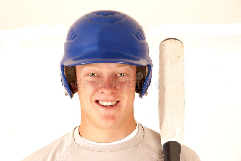 Basebollspelarestående som ler det hållande slagträet royaltyfri fotografi