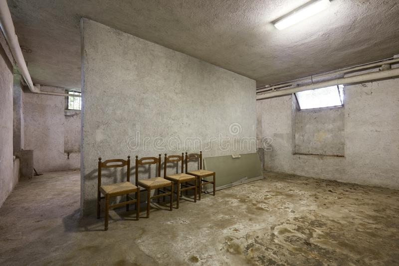 Basement with chairs and dirty floor in old house. Interior stock photo