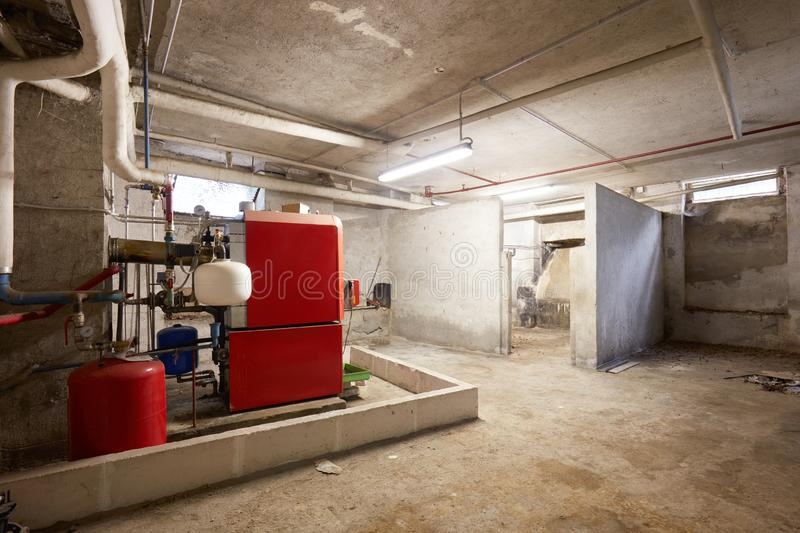 Basement with red heating boiler and dirty floor in old house interior. In Europe royalty free stock photos