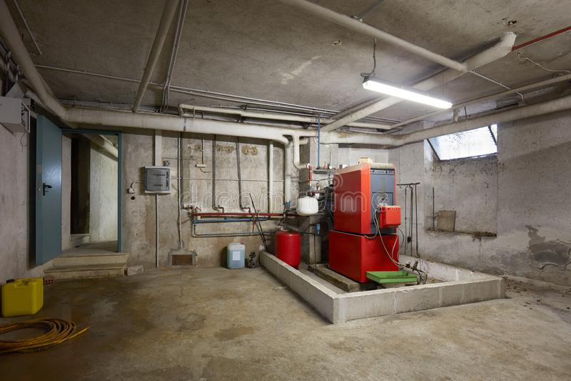 Basement with red heating boiler in old house interior. In Italy royalty free stock photography