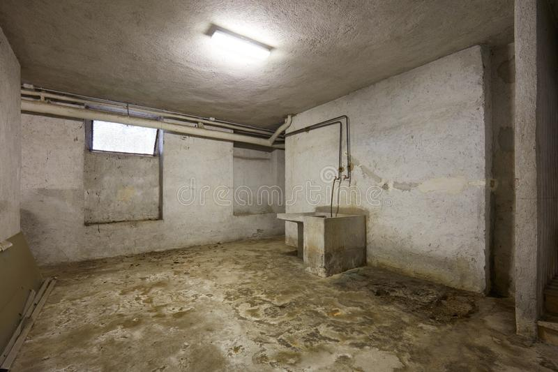Basement with sink and dirty floor in old house interior. In Italy stock photography