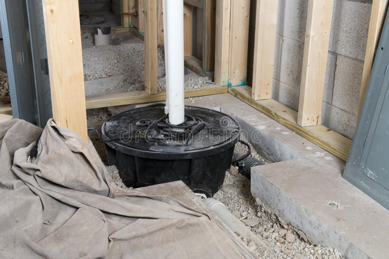 Basement Sump Pump Crock Home Improvement. A new sump pump and crock is being installed in a basement for a home improvement and remodel project stock image