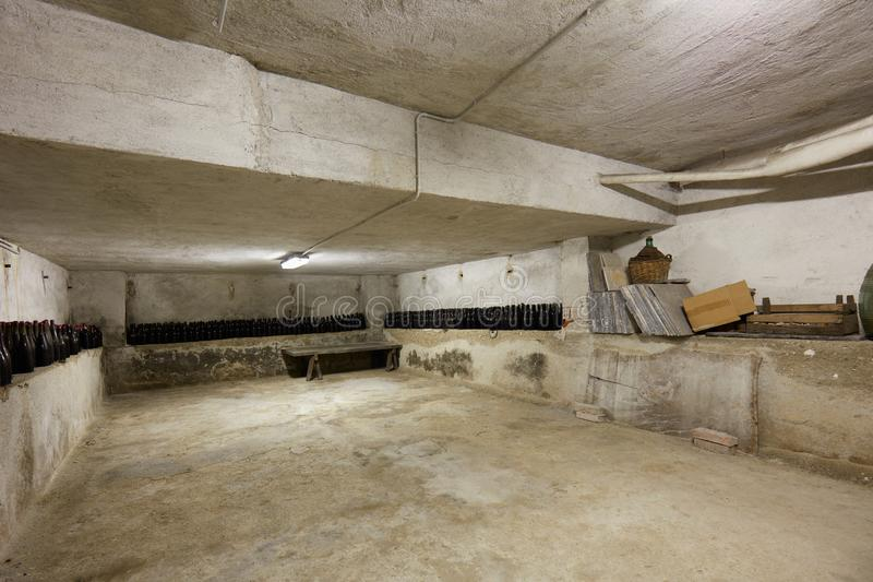 Basement with wine bottles in old house interior. In Italy stock photography
