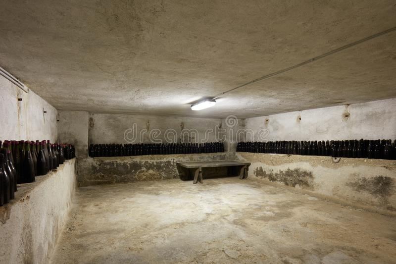 Basement with wine bottles and wooden table in old house interior. In Italy stock photo