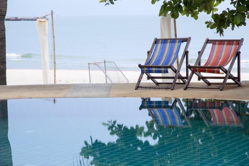 Basen i pokładu krzesło pod kokosowymi drzewkami palmowymi przy kurortem z pięknym dennym widokiem obraz stock